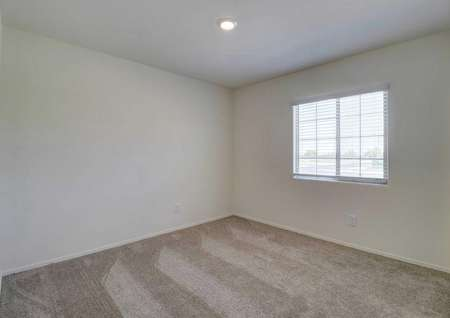 A spare bedroom in the Guadalupe floor plan with light brown carpet, white baseboards and walls with a window on one of them.