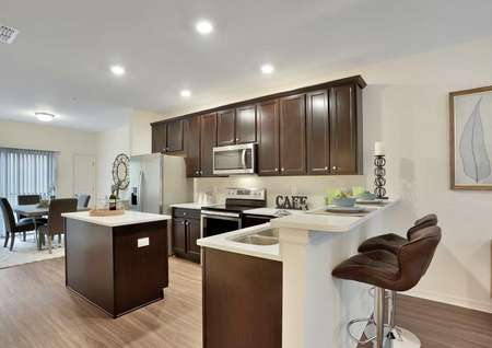 The Pine Key floor plans kitchen that has brown cabinets, stainless steel appliances and a kitchen island.