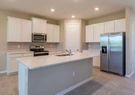 The Sorrento floor plan kitchen has tile flooring, recessed lighting, quartz countertops and islands with a sink.