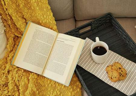 Trace home plan with open book, coffee mug, and cookies