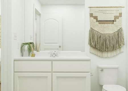 Rendering of   bathroom with white accents, mirror above sink, and toilet.