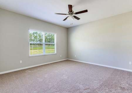 The master bedroom in the Alafia floor plan that has a large window, carpet flooring and a ceiling fan.