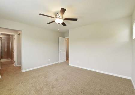 The Northwest Cypress master bedroom is shown with brown carpet and ceiling fan with master bathroom entrance.