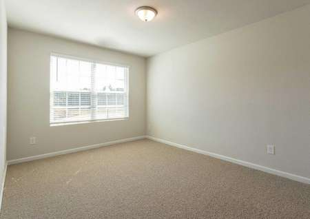Hartford bedroom with large window, brown carpet, and off white walls