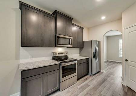 Ozark kitchen finished with stainless steel appliances, brown wood cabinets, and light granite counters