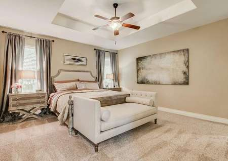 Master bedroom with two windows, ceiling fan, carpet and vaulted ceiling.