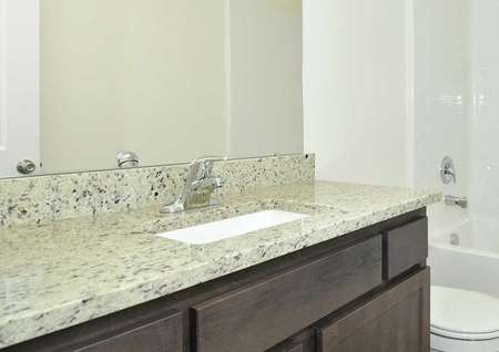 Cypress bathroom with granite counters, undermount sink, and white fixtures