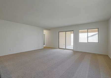 Spacious family room with tan carpet and access to the back yard.