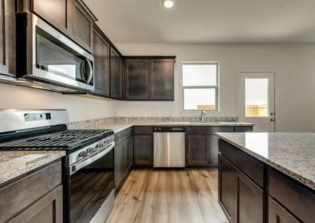 The kitchen has sprawling granite countertops, stainless steel appliances and a gas stove.