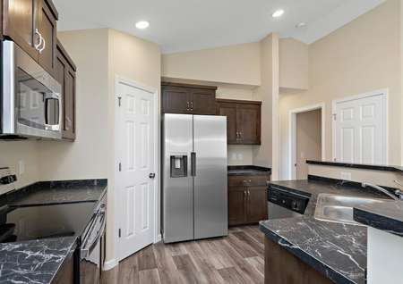 Kitchen with plank flooring, stainless appliances, brown cabinets with brushed nickel hardware and dark gray countertops.