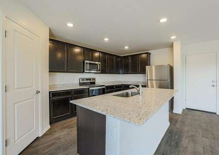 Incredible designer kitchen with stainless steel appliances, granite countertops and a kitchen island with an undermount sink.