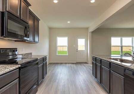 Cypress kitchen with black stove, oven, and microwave, granite countertops, and brown cabinetry