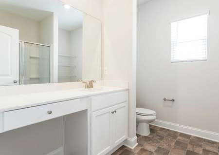 Allatoona master bathroom with tile flooring, white trim, and large vanity with makeup counter