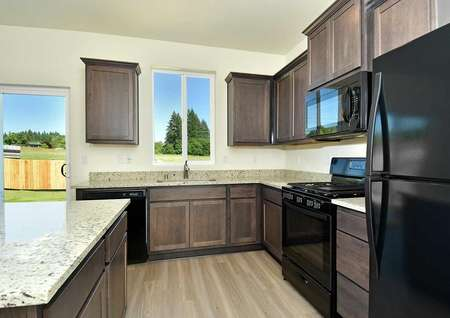 Cypress kitchen with custom cabinets, stone finish countertops, and wood style floors