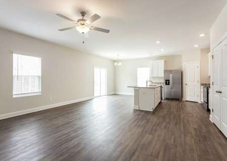 Avery great room with ceiling fan, wood look flooring, and kitchen island