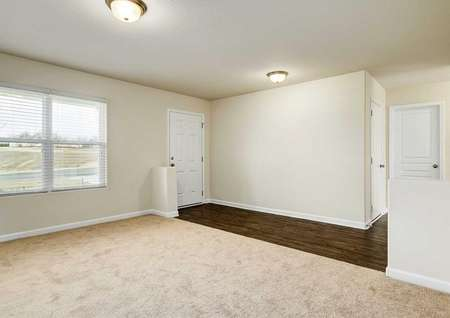 Hartford great room with carpet floors, large windows, and front door