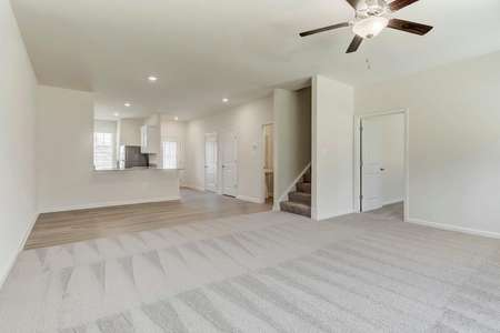 Spacious open concept living, dining, kitchen with ceiling fan
