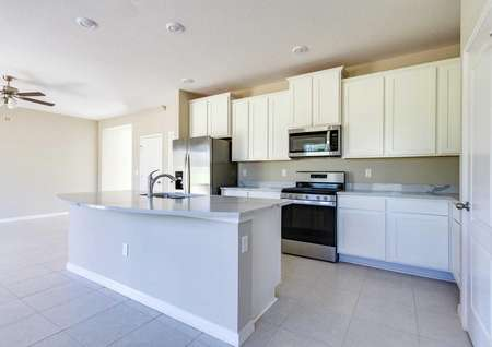 Kitchen with quartz countertops, stainless steel appliances, tile floors and an island in the St. Johns floor plan.
