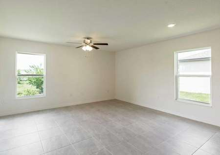 Spacious living room with tile flooring, white walls, a ceiling fan and a sliding glass door in the Anastasia floor plan.