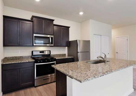 New kitchen with stainless steel oven and microwave, granite counters, and brown cabinets