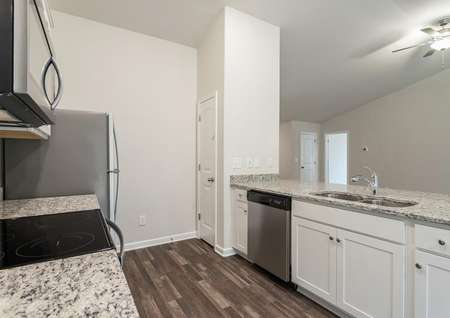 Kitchen with stainless appliances, vinyl plank flooring, white cabinets and granite countertops.