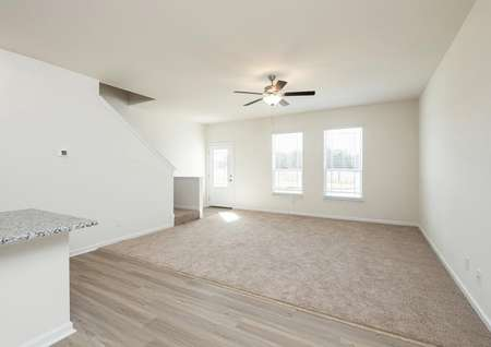 Spacious living room with carpet, ceiling fan and two windows near entry with glass front door.