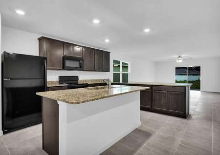 St. Martin plan's kitchen with granite countertops, an island that has a sink, black kitchen appliances and tile flooring.