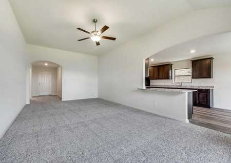 Whichita great room with ceiling fan, light grey carpet, and kitchen counter