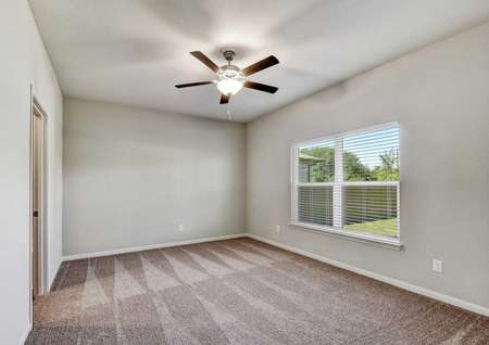 Victoria bedroom finished with brown carpet, white baseboards and window frame, and overhead brown ceiling fan