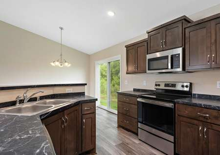 Kitchen with rich dark brown cabinetry, stainless appliances, chrome hardware, light plank flooring and a decorative light fixture hanging in the adjacent dining room.