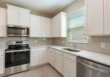 The kitchen in the Calabria floor plan has stainless steel appliances, white cabinets, a sink and tile flooring.
