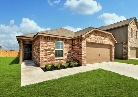 Medina single-family home with green landscaped yard, brick finish siding, and brown two car garage door