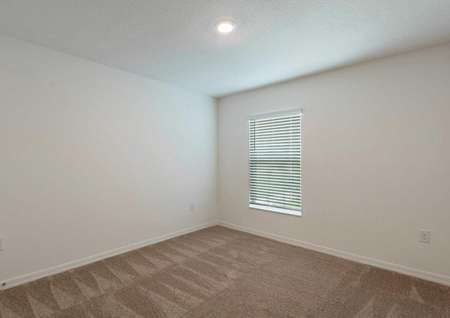 Carpeted spare room in the Cocoa floor plan with brown carpet flooring, white wallsand a single hung window covered by blinds.