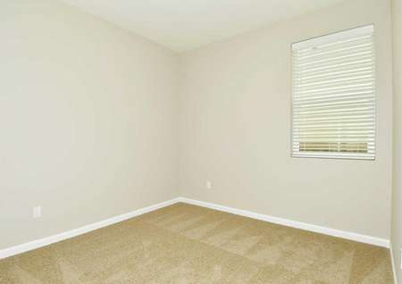 The Northwest Aspen second bedroom is shown with brown carpet and a window with blinds.