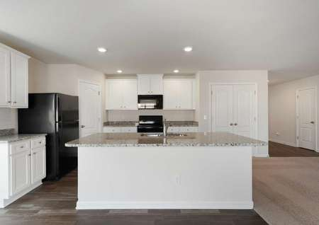 Camden kitchen with black appliances, granite counters, and large kitchen island with sink