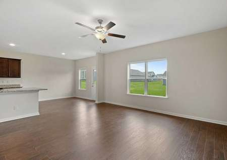 View of the Cypress model's living room accenting the vinyl wood like flooring, large windows and ceiling fan. On the left a glimpse of the kitchen granite countertops and cabinets