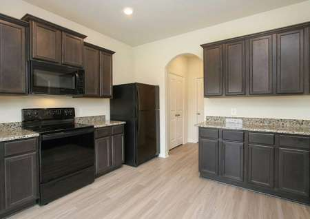 Recessed lighting, vinyl wood-style floors, granite counters, black appliances, and dark cabinets in the Rayburn plan kitchen