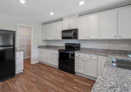 Allatoona kitchen with rich granite counters, white finish cabinetry, and black appliances