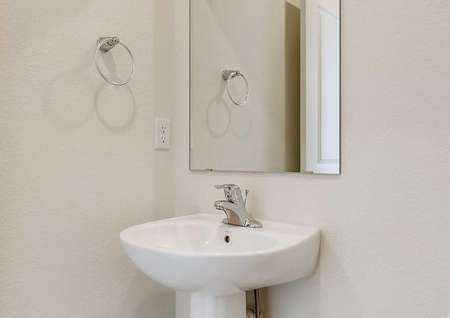 Downstairs half-bathroom, featuring the single sink with a mirror above it.