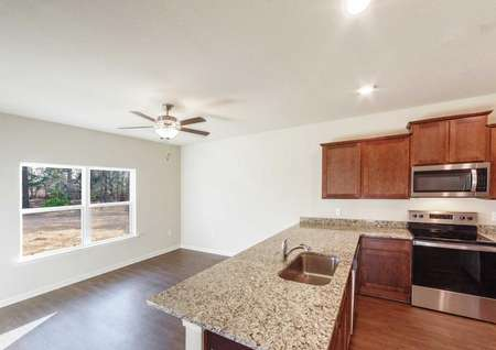 Kitchen with granite countertops overlooking a family room with plenty of natural light entering the home.