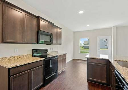 The Cypress floor plan's kitchen layout showing the granite countertops, dark brown cabinets, recessed lighting, stainless steel sink, and vinyl flooring. Also shown on the back wall a door and window facing outdoors