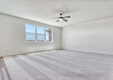 The living room in the Jasmine floor plan with a ceiling fan that has a light, carpet flooring and multiple windows.