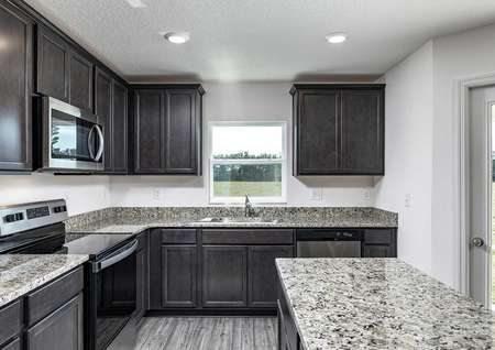 Close-up view of kitchen's granite countertops, installed appliances and incredible cabinet space.