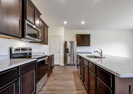 Rio kitchen with wood flooring, light colored ceramic countertops, and stainless steel oven, stove, and microwave