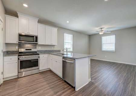 The kitchen in the Crystal floor plan with stainless steel appliances, granite countertops and wood-like flooring.
