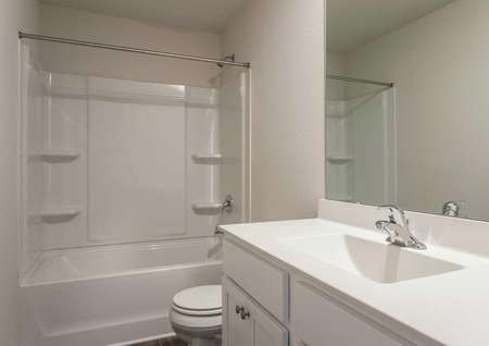 Madison guest bathroom with white cabinets, modern fixtures, and a tub/shower unit