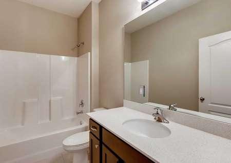 Secondary bathroom in the Santa Maria model home. White shower and tub combo, cultured marble countertops and dark brown cabinets