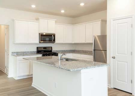 Close up of kitchen with white cabinets, granite counters, stainless refrigerator, gas range and microwave.