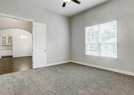 Bradley finished floor plan with grey carpeting, white on grey walls, and window with blinds