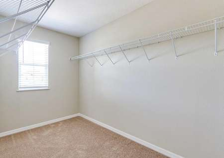 A large walk-in closet with a window, light brown carpet, white baseboards and tan walls in the St. Johns floor plan.